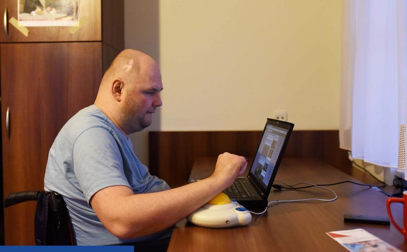 Zdjęcie wykonane w pokoju. Przy brązowym blacie biurka siedzi młody mężczyzna na wózku inwalidzkim. Widzimy jego prawy profil. Głowa ogolona, lekki zarost. Przed nim otwarty laptop. Nadgarstek prawej ręki spoczywa na żółtej kulce od myszki przystosowanej dla osób, które mają niesprawne dłonie. Za nim po lewej widać brązowe drzwi szafy.