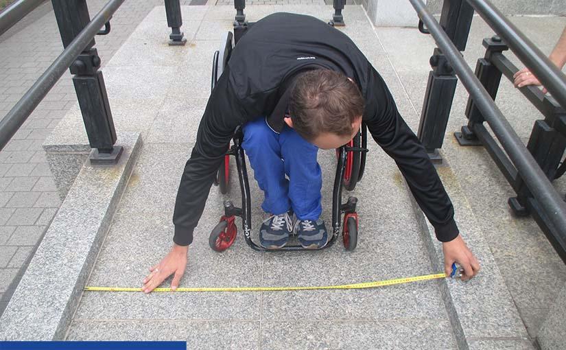 Zdjęcie wykonane na podjeździe dla osób z niepełnosprawnością. W centrum przodem do nas stoi mężczyzna na wózku, który schyla się (nie widać jego twarzy tylko rzedkie ciemne włosy), aby metrówką zmierzyć szerokość podjazdu. Ubrany jest w czarną kurtkę, niebieskie spodnie i sportowe buty.