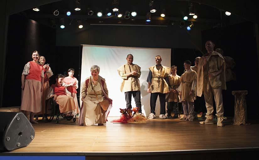 Scena, na której występują aktorzy z niepełnosprawnością ubrani w proste lniane stroje. Na suficie widać profesjonalne oświetlenie, prawa część zdjęcia zacieniona.