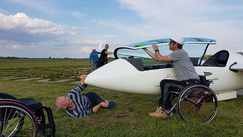 Zdjęcie wykonane na otwartej przestrzeni. Na trawie po prawej stronie widać przednią część szybowca. Przed nim stoi młody chłopak na wózku, który uchyla kabinę. Pod dziobem leży dorosły mężczyzna z nogami amputowanymi poniżej kolan. Leży na prawym boku i lewą ręką wyciera kadłub maszyny.