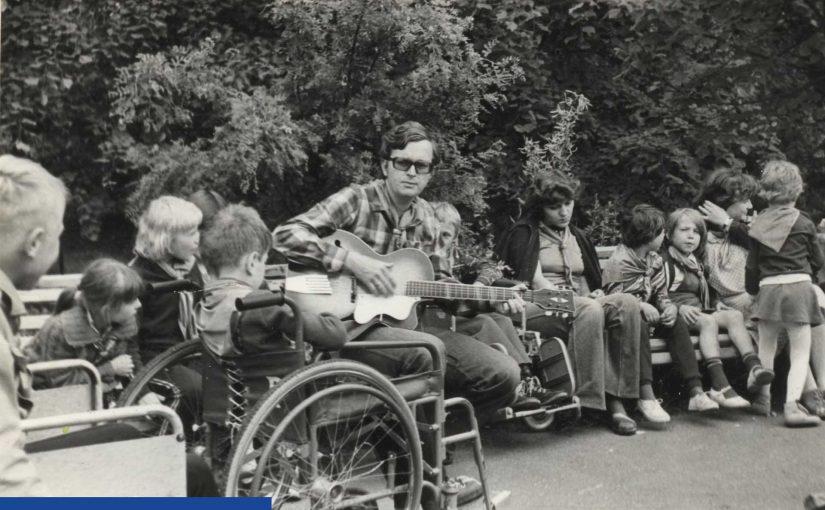 Archiwalne, czarno - białe zdjęcie. Na ławce zwrócony do obiektywu siedzi młody mężczyzna w ciemnych okularach. Gra na gitarze. Po jego lewej stronie widać dzieci na dużych, pokojowych wózkach. Po prawej inne dzieci siedzą na ławkach.