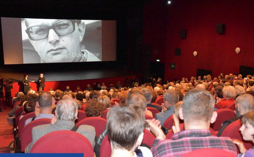 """Zdjęcie wykonane zza ostatnich rzędów sali kinowej. Widać pełną salę widzów, którzy zwróceniu są w kierunku ekranu - na nim czarno - białe ujęcie - twarz młodego mężczyzny w okularach i tytuł """"Doktor Piotr"""" w prawym dolnym rogu."""