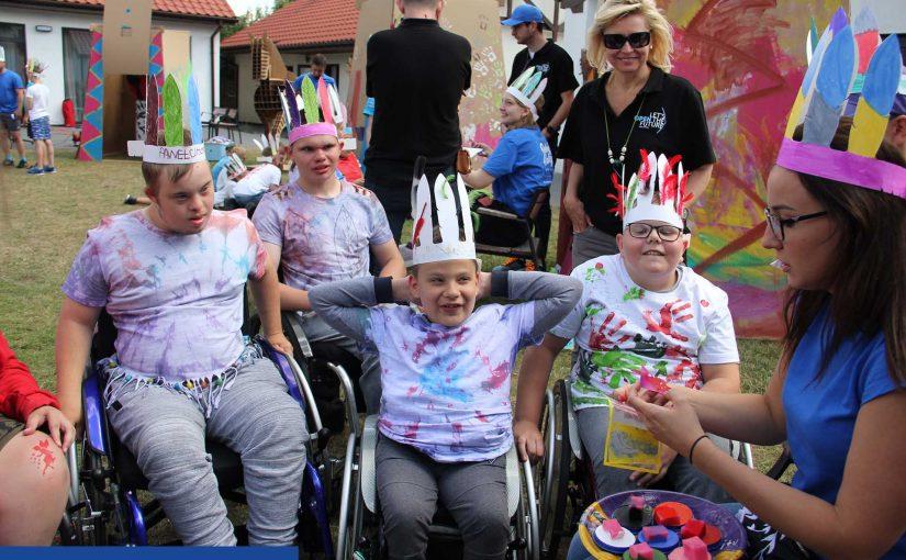 Na zdjęciu czterech chłopców na wózkach w wieku ok. 10-12 lat. Mają na sobie pomalowane na kolorowo T-shirty, a na głowach tekturowe pióropusze. Są bardzo zadowoleni. W tle widać kolorowe tipi również z tektury.