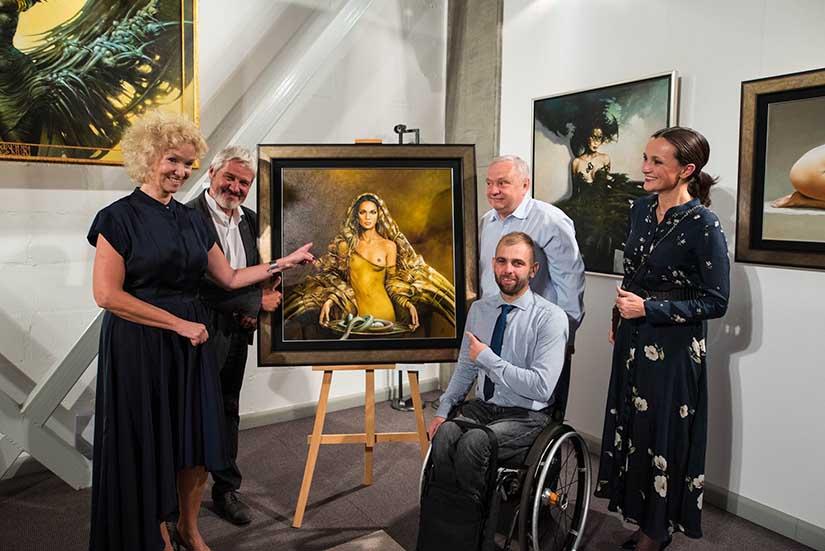 Zdjęcie wykonane w galerii sztuki. W centrum obraz na sztaludze w złotej ramie przedstawiający nagą kobietę. Po lewej stronie Violetta Kowalczyk i Karol Bąk, po prawej - Zuzanna Janaszek - Maciaszek, Marek Bystrzycki siedzący na wózku oraz właściciel obrazu.  Wszyscy radośni.