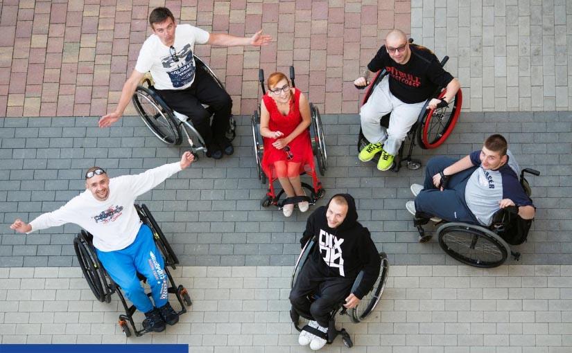 Zdjęcie wykonane z góry (prawdopodobnie z okna). Sześć młodych osób na wózkach inwalidzkich (w tym jedna kobieta w czerwonej sukience bez rękawów) patrzy w górę. Dwie osoby z lewej wyciągają na boki ręce w geście pozdrowienia.