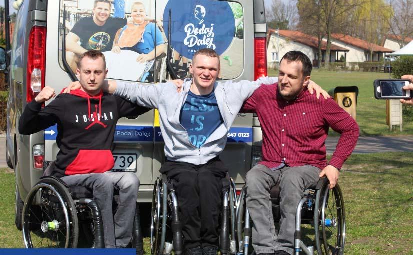 Trzech młodych mężczyzn na wózkach stoi obok siebie. Środkowy blondyn zarzuca ramiona na stojących po bokach kolegów. Od razu za nimi widać tylne drzwi busa, a na nich po prawej stronie logo Fundacji PODAJ DALEJ, a po lewej zdjęcie Filipa Chajzera z chłopcem na wózku.