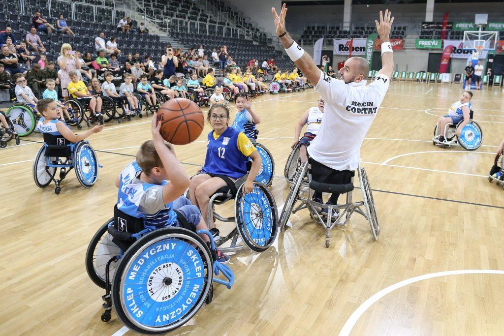 Mecz koszykówki na wózkach. Na boisku odwrócony tyłem z podniesionymi rękoma jest Marcin Gortat (również siedzi na wózku), a wokół niego dzieci. Chłopiec z lewej strony trzyma piłkę do koszykówki nad głową - ujęcie tuż przed rzutem.