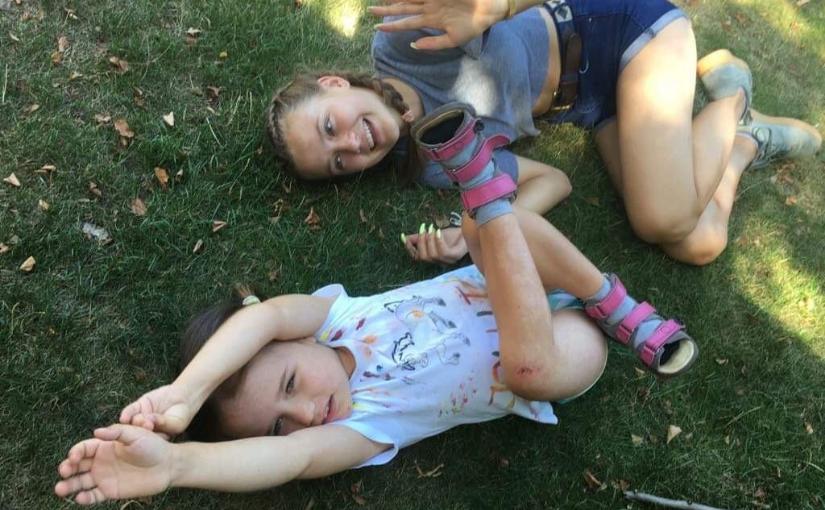 Zdjęcie wykonane z góry. Na trawie leży na plecach mała dziewczynka z wyciągniętymi nad głowę rączkami, na nóżkach ma sandały ortopedyczne. Obok niej, w górnej części zdjęcia leży roześmiana wolontariuszka. Obie ubrane w letnie stroje.