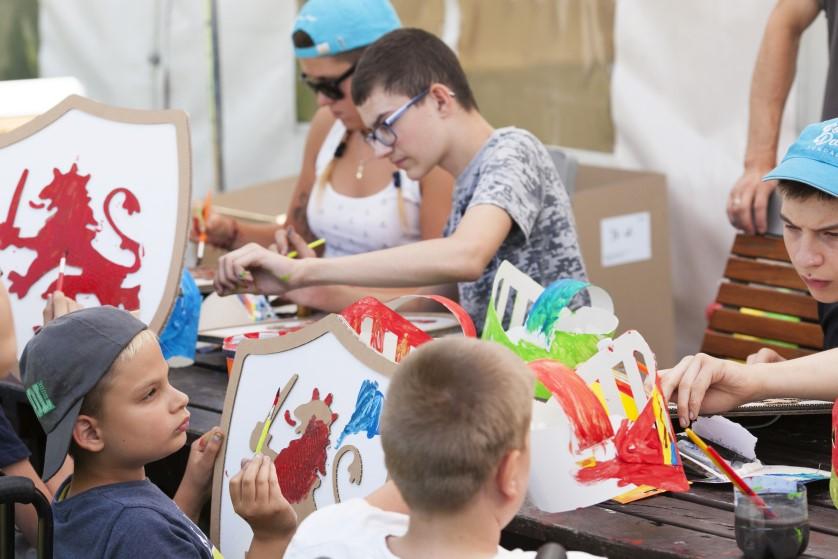 Przy drewnianym brązowym stole siedzą dzieci, które z zaangażowaniem malują farbami tekturowe tarcze i hełmy rycerskie.