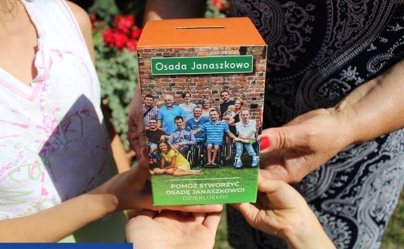 """Cztery kobiece ręce trzymają skarbonkę. Jest na niej zdjęcie przedstawiające grupę uśmiechniętych osób na wózkach inwalidzkich i podpis: """"Pomóż stworzyć Osadę Janaszkowo! Dziękujemy!"""""""