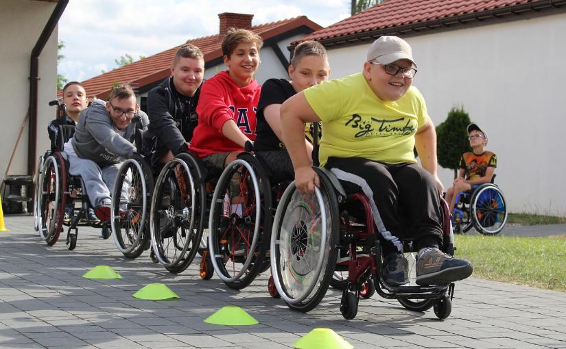Sześcioro chłopców na wózkach inwalidzkich stworzyło pociąg - jadą jeden za drugim. Uśmiechnięci, widać, że dobrze się bawią!