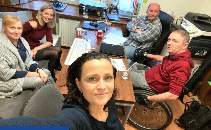 Na pierwszym planie w centrum kobieta, za nią w gabinecie przy stole po prawej siedzą dwie kobiety, po lewej dwóch mężczyzn (z czego jeden na wózku). Zdjęcie typu selfie wykonane podczas zebrania.