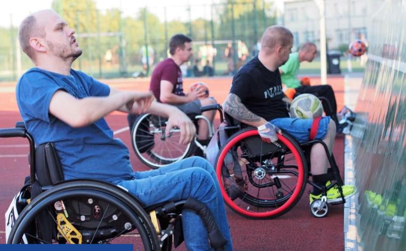 Zdjęcie zrobione na boisku z czerwonym tartanem. Widać czterech mężczyzn na wózkach inwalidzkich, którzy stoją bokiem. Po prawej stronie widoczna ściana, o którą odbijają piłki.