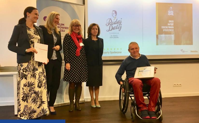 Po lewej stronie stoją cztery kobiety elegancko ubrane, po prawej na wózku inwalidzkim siedzi mężczyzna, który na kolonach trzyma antyramę z informacją o nagrodzie. W tle na ekranie widać okładkę Raportu Fundacji PODAJ DALEJ za 2017 rok i logo Fundacji.