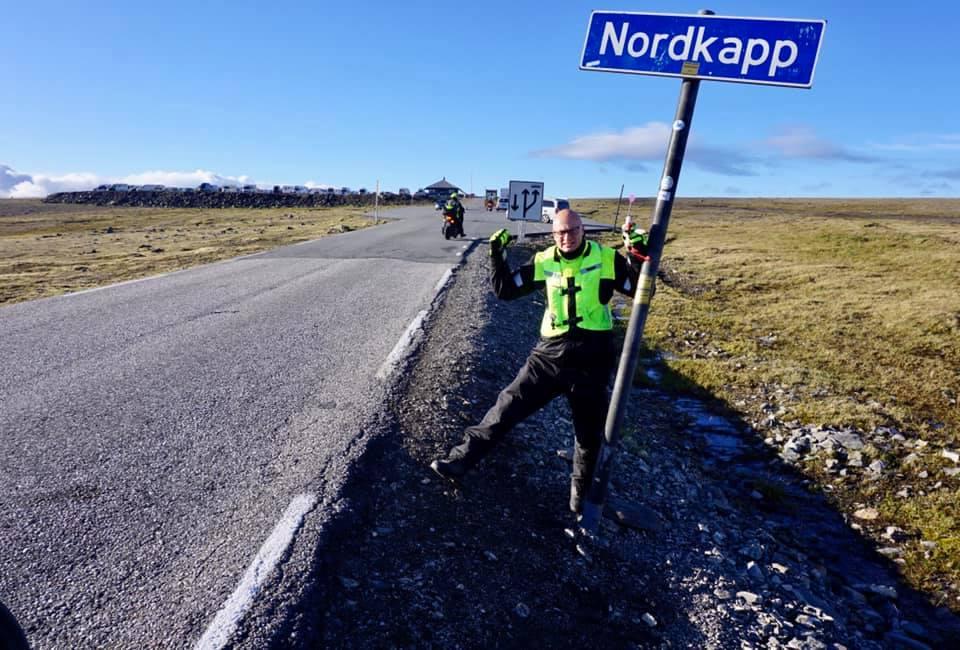 """Zdjęcie wykonane przy włąskiej asfaltowej drodze. Po prawej stronie znak drogowy z napisem """"Nordkapp"""" (białe litery na niebieskim tle). Przy znaku stoi uśmiechnięty młody łysy mężczyzna w okularach i w stroju motocyklowym (czarne spodnie, odblaskowa kamizelka). Lewą ręką opiera się o znak, w prawą wznosi w geście zwycięstwa.  Po obu jego stronach widać równinę porośniętą krótką trawą i czyste błękitne niebo."""