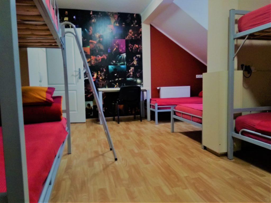 Wnętrze pokoju w hostelu. Po lewej i prawej stronie widać fragmenty piętrowych łóżek, dalej po prawej stronie dwa pojedyncze łóżka na metalowych ramach w szarym kolorze. Wszystkie łóżka przykryte czerwonymi prześcieradłami. Na ścianie na wprost widać ciemną fototapetę przedstawiającą sceny z koncertów muzycznych. Na tle ściany widać białe otwarte drzwi. Podłoga z jasnych drewnianych paneli.