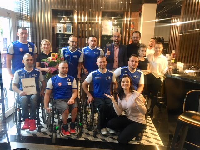 Grupa 14 radosnych osób pozuje do zdjęcia we wnętrzu salonu fryzjerskiego. Czterech mężczyzn siedzi na wózkach inwalidzkich. Oni oraz oraz trzech mężczyzn, którzy za nimi stoją są ubrani w niebiesko białe zawodnicze koszulki. Pozostałe osoby - kobiety i mężczyźni ubrani elegancko.
